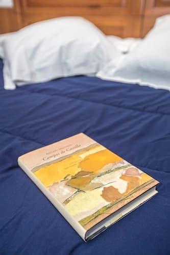 Detalles de una fotografia del llibro campos de castilla sobre una cama del Hostal Vitorina